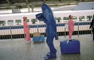 André Kuenzy, alias Blue Man, reiser verden rundt i sitt blå gummikostyme. Her er han på en jernbanestasjon i Japan. Videoene viser hvordan folk reagerer på et vesen så forskjellig fra dem selv. Foto: André Kuenzy